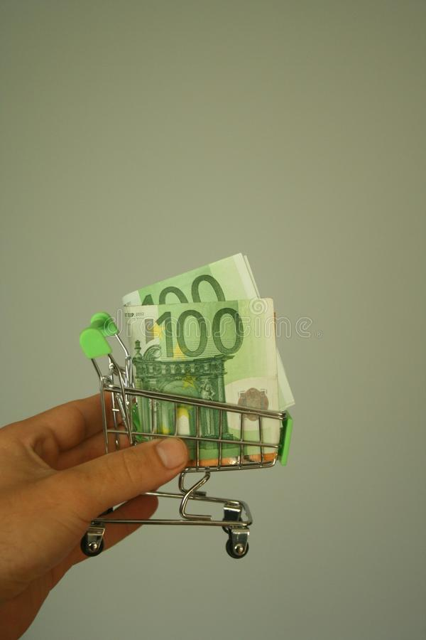 Mini dummy shopping cart in human hand with paper euro banknotes as a concept for online shopping, saving, business and making mon. A mini dummy shopping cart in royalty free stock photo