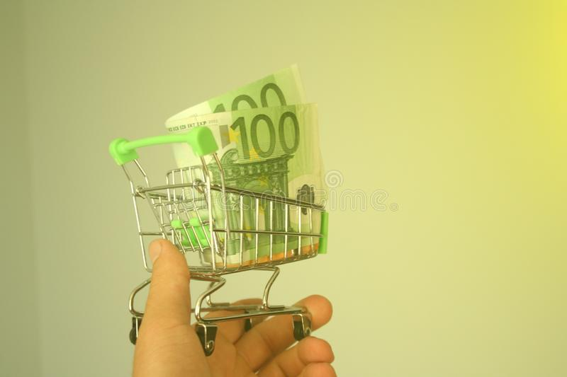 Mini dummy shopping cart in human hand with paper euro banknotes as a concept for online shopping, saving, business and making mon. A mini dummy shopping cart in royalty free stock image