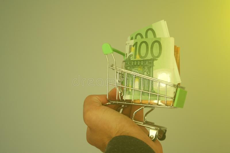 Mini dummy shopping cart in human hand with paper euro banknotes as a concept for online shopping, saving, business and making mon. A mini dummy shopping cart in royalty free stock images