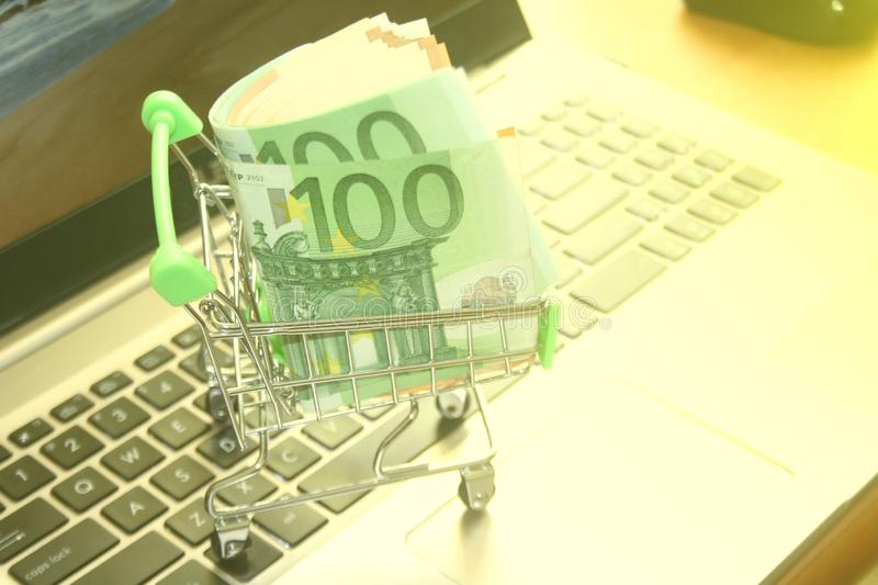 Mini dummy shopping cart on laptop with paper euro banknotes as a concept for online shopping, saving, business and making money a. A mini dummy shopping cart on stock photo