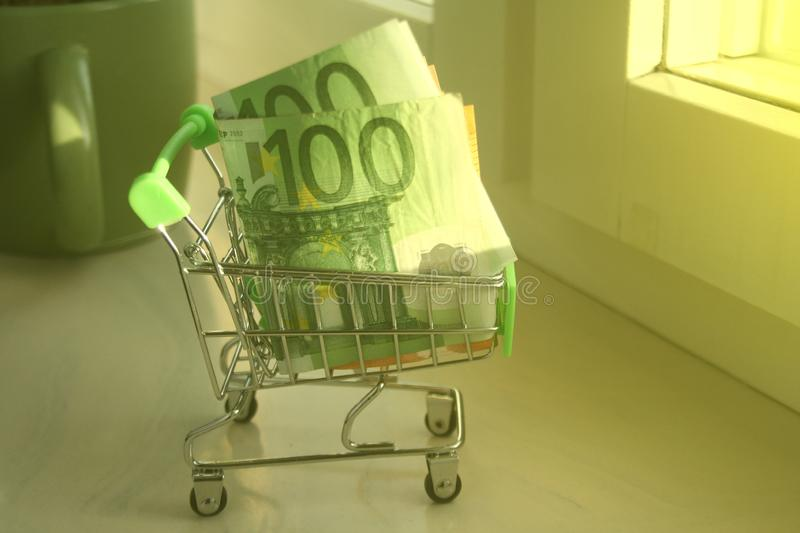 Mini dummy shopping cart  with paper euro banknotes as a concept for online shopping, saving, business and making money as well as. A mini dummy shopping cart stock images