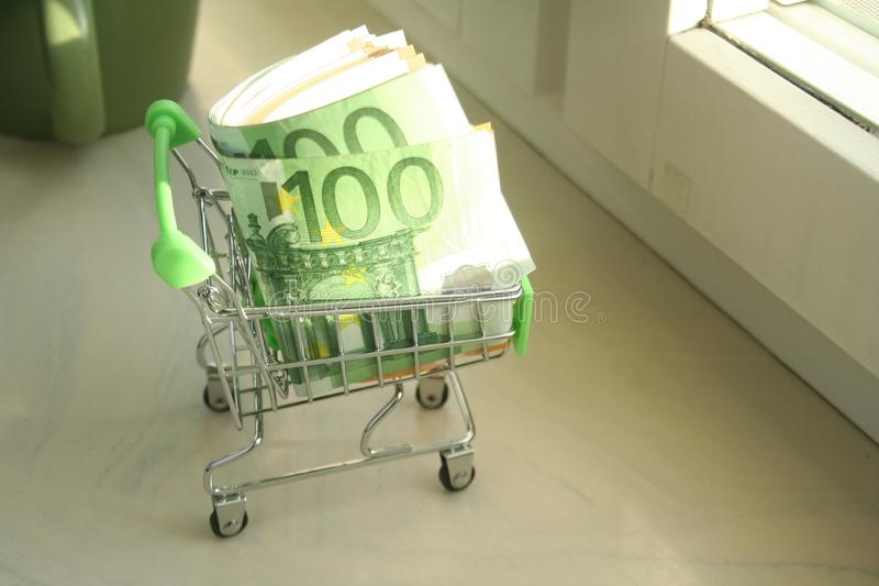Mini dummy shopping cart in human hand with paper euro banknotes as a concept for online shopping, saving, business and making mon. A mini dummy shopping cart royalty free stock photos