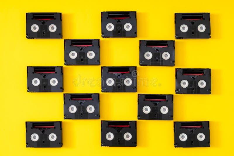 Mini-DV Kassetten der Weinlese verwendet für zurück filmen in einem Tag Muster gemacht von den Plastikvideobändern auf gelbem Hin lizenzfreie stockbilder