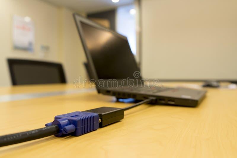 Mini-DVI do portátil ao projetor video do cabo de VGA na tabela de madeira na sala de reunião foto de stock