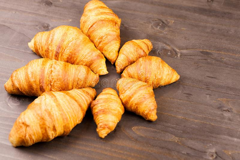 Mini e maxi croissant che si trovano sulla tavola di legno immagine stock