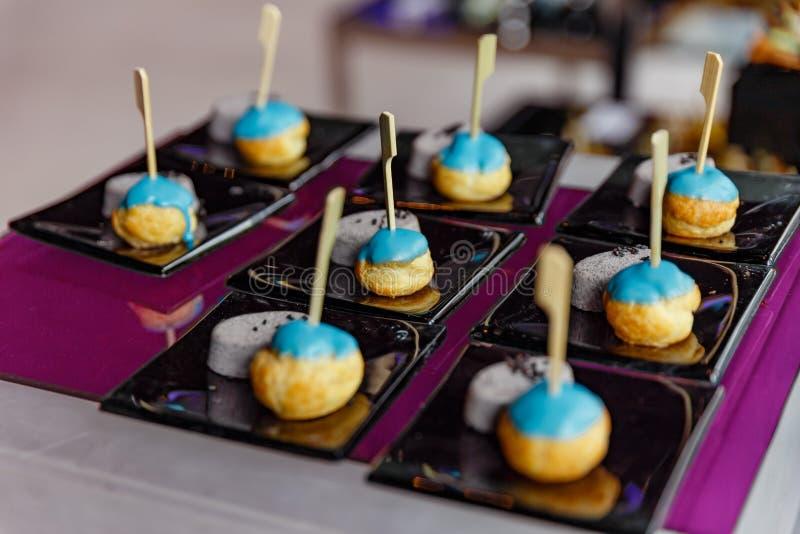 Mini Eclair Glazed com açúcar azul da cor serviu com o Taro doce do esmagamento e sésamo preto fotografia de stock royalty free