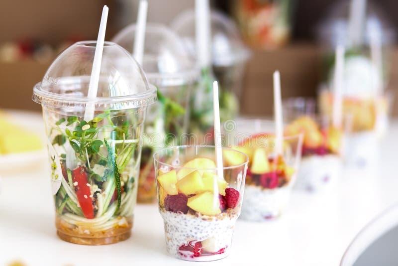 Mini- efterrätter och den sunda grönsaken microgreen sallader i plast- koppcanaps Sköta om den tjänade som tabellen arkivbild