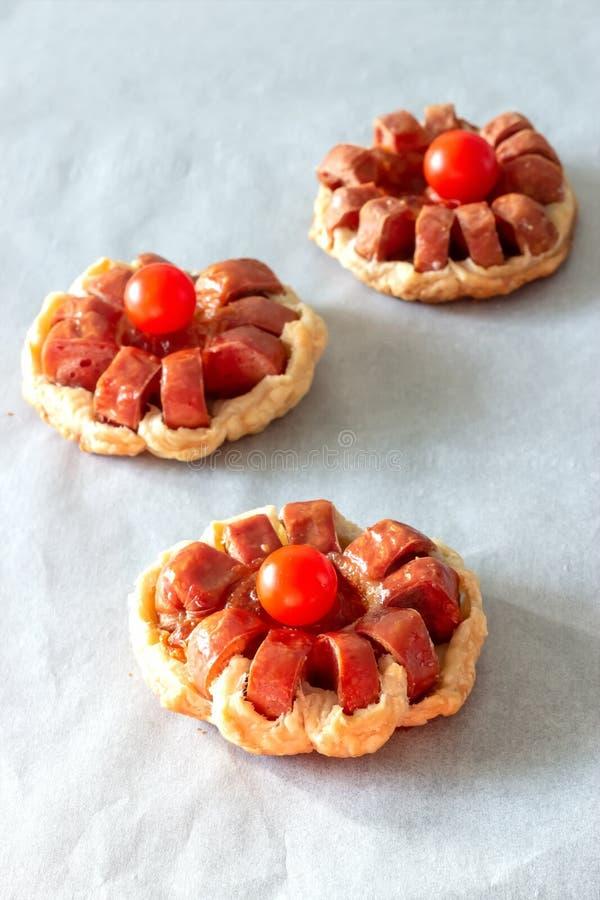 Mini empanada de la pasta de hojaldre con el tomate de la salchicha y de cereza Fondo de papel de la hornada Foco selectivo Copie fotografía de archivo libre de regalías