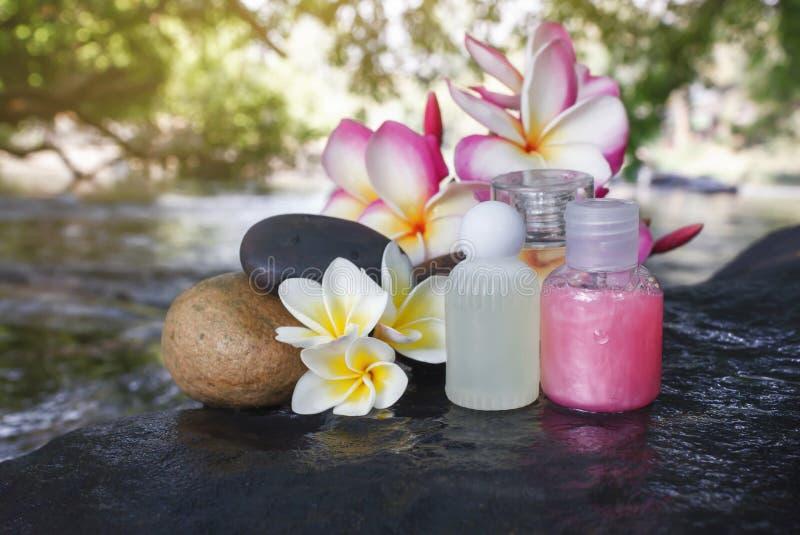 Mini ensemble de liquide de gel de douche de bain moussant avec les fleurs et le pebbl images stock