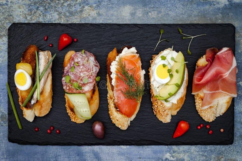 Mini ensemble de nourriture de sandwichs Brushetta ou tapas espagnols traditionnels authentiques pour la table de déjeuner Casse- photos libres de droits