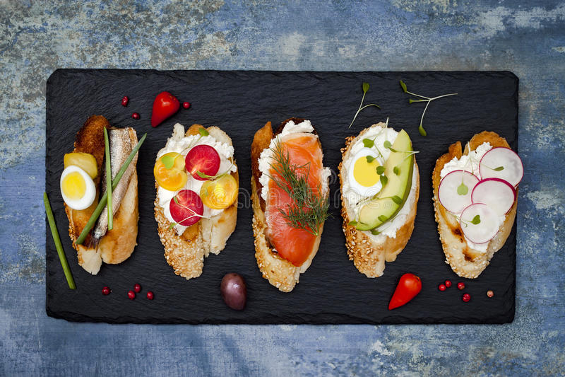 Mini ensemble de nourriture de sandwichs Brushetta ou tapas espagnols traditionnels authentiques pour la table de déjeuner Casse- image stock