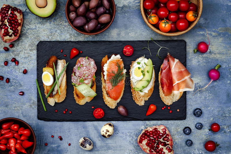 Mini ensemble de nourriture de sandwichs Brushetta ou tapas espagnols traditionnels authentiques pour la table de déjeuner Casse- photographie stock libre de droits