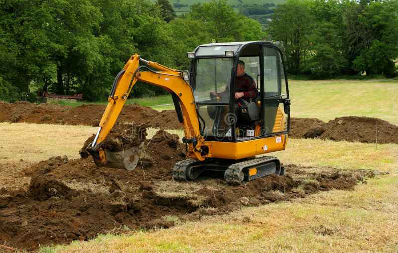 Mini escavador na ação imagem de stock royalty free