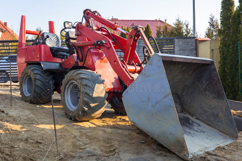Mini escavadora estacionada no ouse para o trabalho à terra imagens de stock