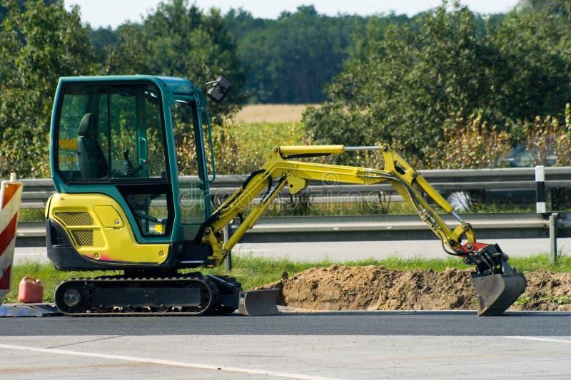 Mini escavatore sull'autostrada fotografia stock
