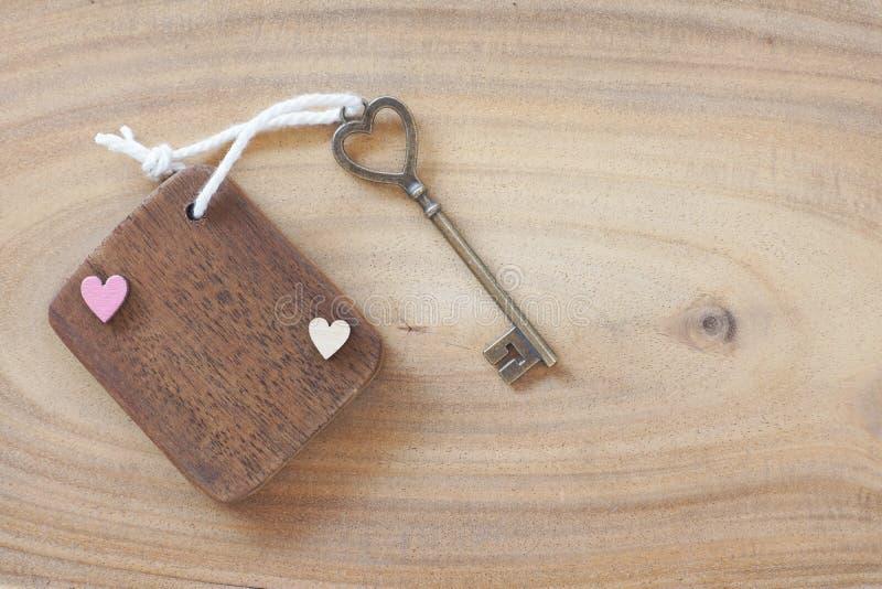 Mini etichetta di legno con la bella chiave antica di forma del cuore su fondo di legno Benvenuto alla nuova casa, concetto della immagine stock libera da diritti