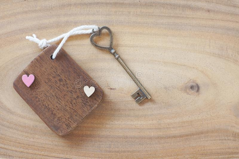 Mini etiqueta de madeira com chave antiga bonita da forma do coração no fundo de madeira Boa vinda à casa nova, conceito doce da  imagem de stock royalty free