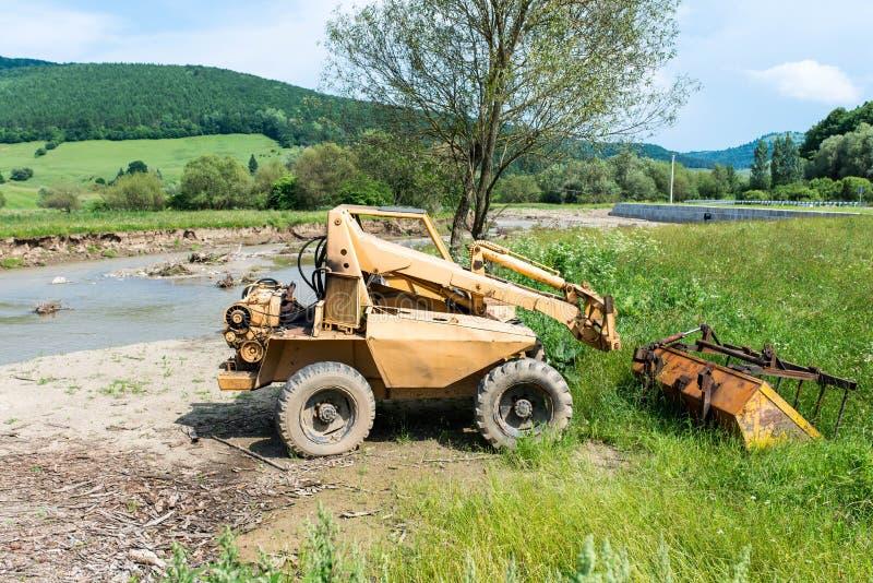 Mini excavador abandonado, viejo cerca de un pequeño río imagenes de archivo