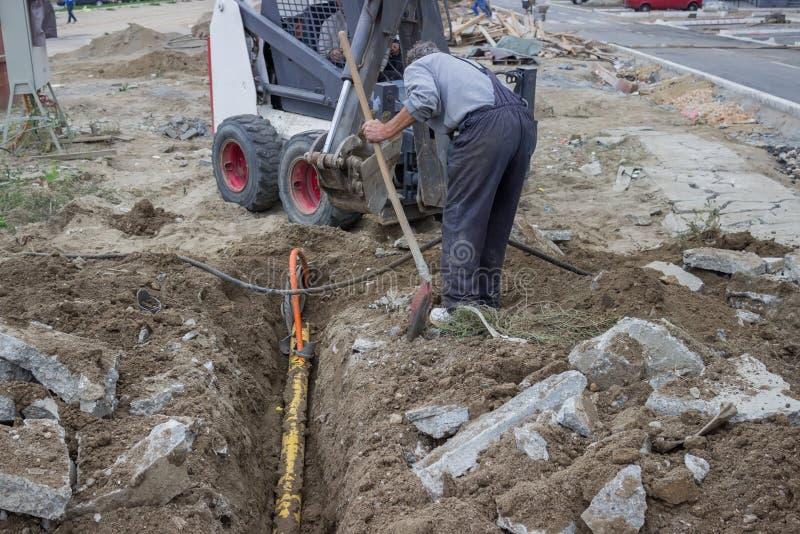 Mini excavador desenterrando los cables eléctricos del foso 3 imagenes de archivo