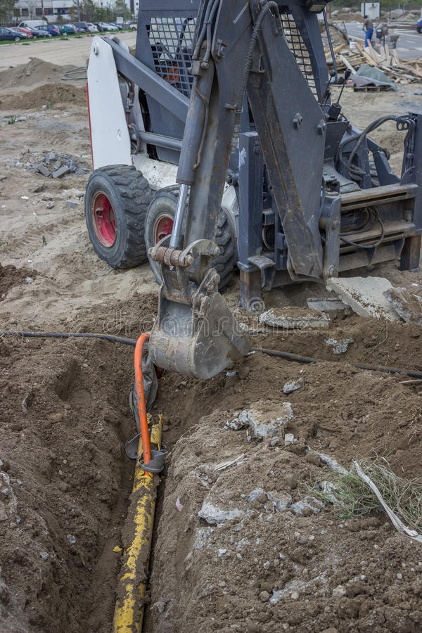 Mini excavator digging up a electrical cables from trench. At construction site stock photo