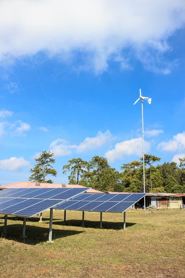 Mini exploração agrícola solar e moinho de vento branco no dia fresco fotos de stock royalty free