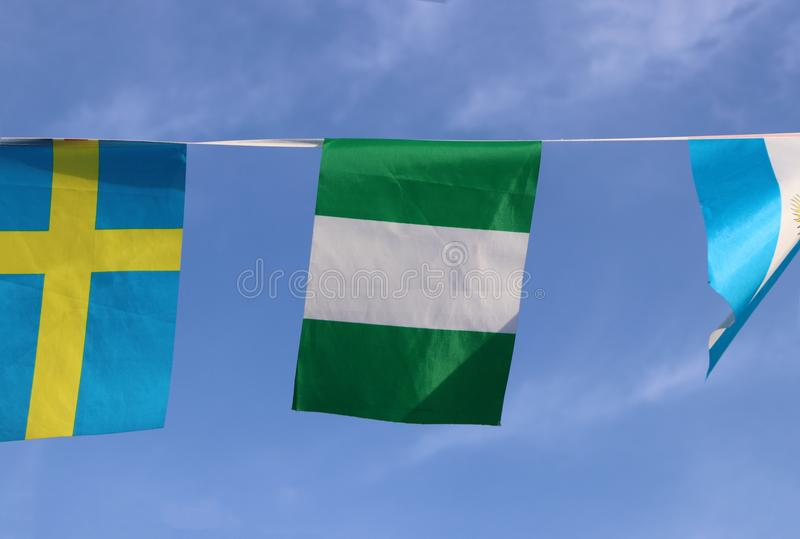 Mini fabric rail flag of Nigeria, the flag has three vertical bands of green, white, green. The two green stripes represent Nigeria`s natural wealth, while the stock image