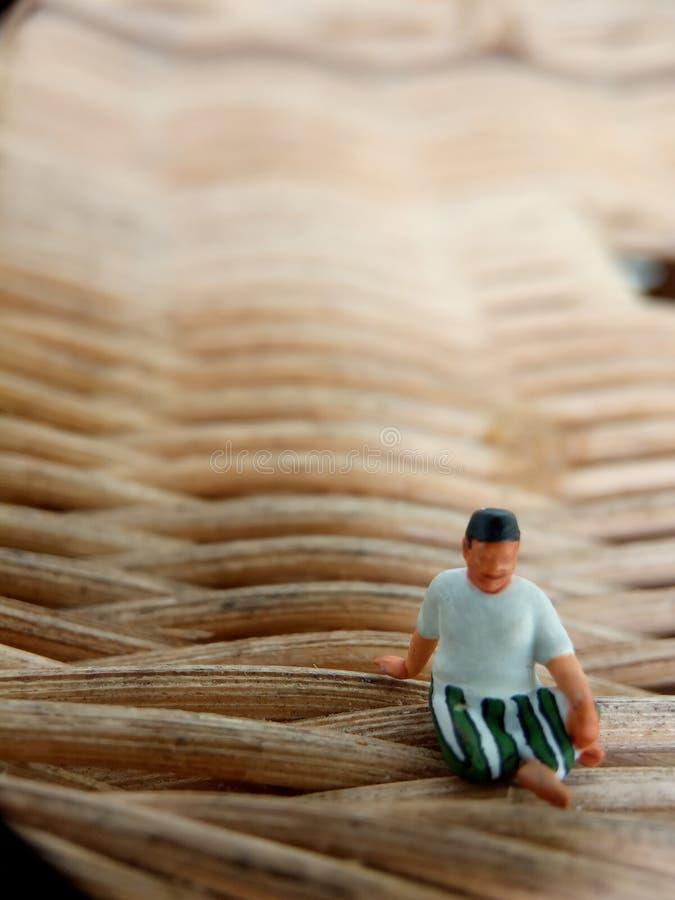 A mini figura ancião indonésio da foto ascendente próxima do brinquedo que usa o sarung, o kopiah e a camisa branca, senta-se na  fotografia de stock