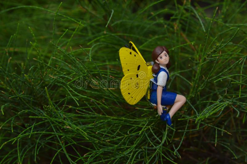 Mini figura di seduta leggiadramente sulle foglie del pino immagine stock