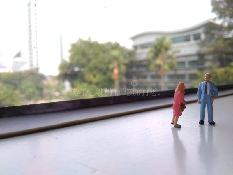 Mini figura homem de negócios e posição da mulher de negócios e fazer uma discussão pequena na janela do trem foto de stock