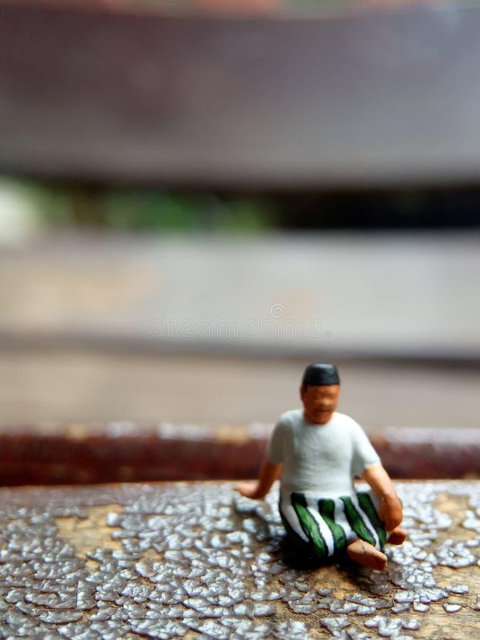 Mini figura viejo hombre del juguete sentarse en la silla de madera del rasguño, con la copia o el espacio negativo para el área  imagen de archivo