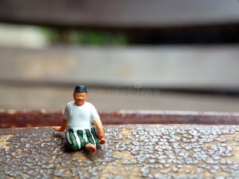 Mini figura viejo hombre del juguete sentarse en la silla de madera del rasgu?o, con la copia o el espacio negativo para el ?rea  fotografía de archivo libre de regalías