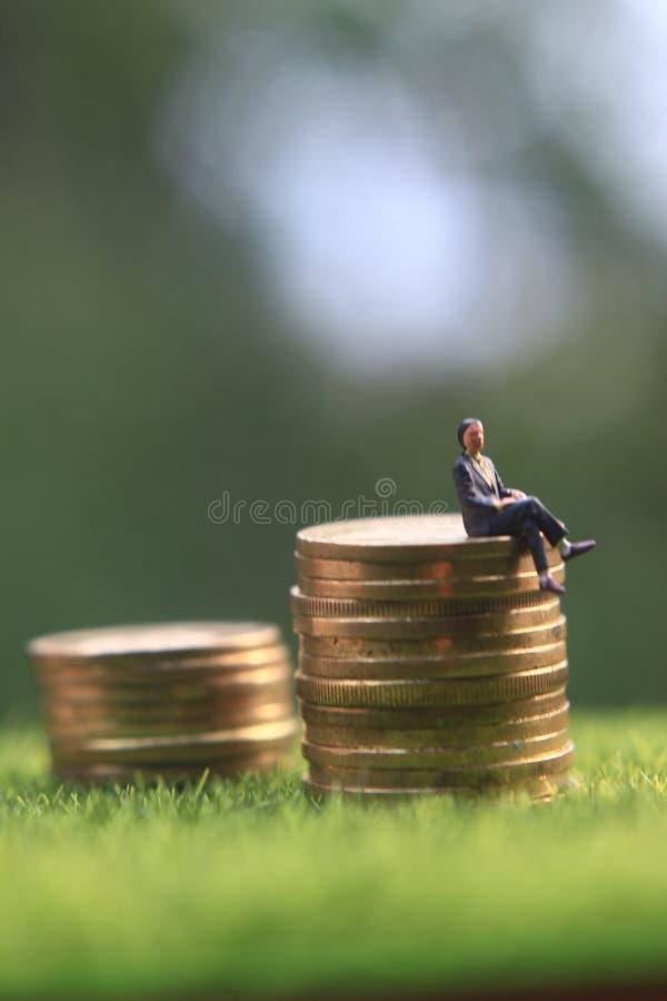 Mini Figure Businessman am Stapel der Münze am frischen grünen Gras sitzend, genießen Sie seinen Finanzerfolg lizenzfreie stockfotografie