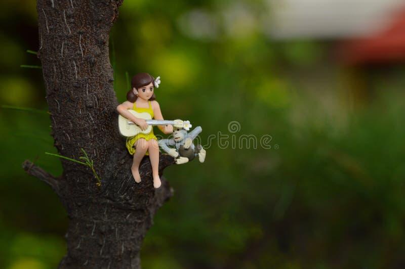 Mini figure della ragazza che giocano chitarra mentre sedendosi sui tronchi di albero fotografia stock