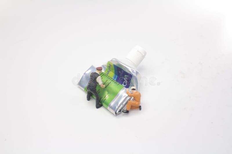mini figure push a Tubes of toothpaste royalty free stock photos