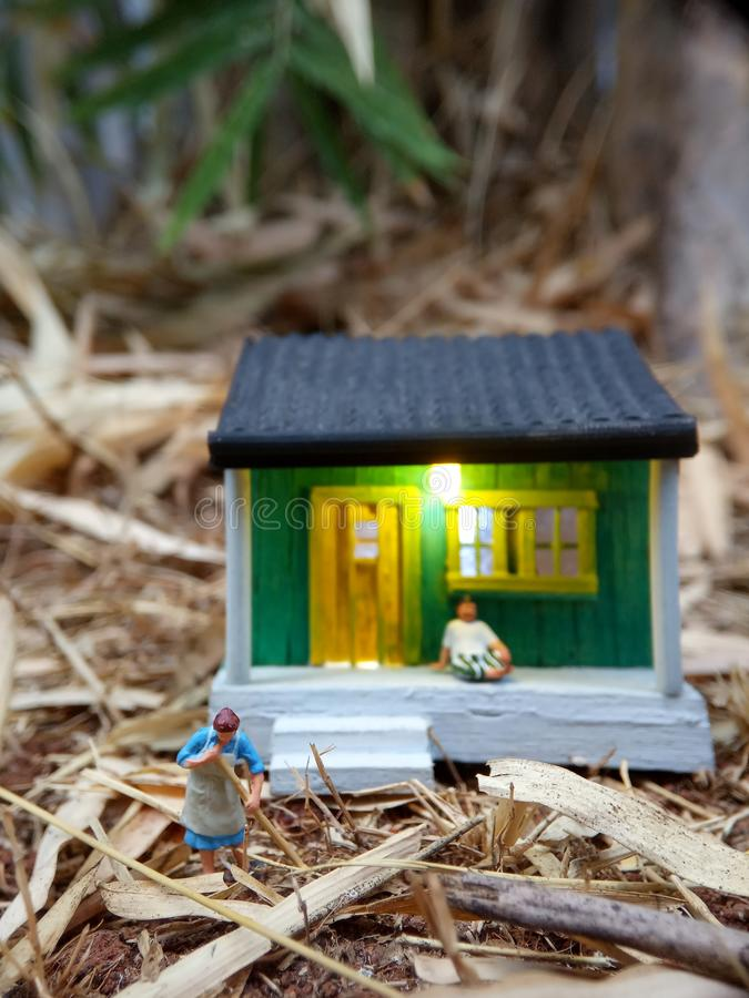 Mini figure toy Indonesian woman cleaning the terrace and old man using sarung, kopiah and white shirt, sit at his house, beyond stock photography