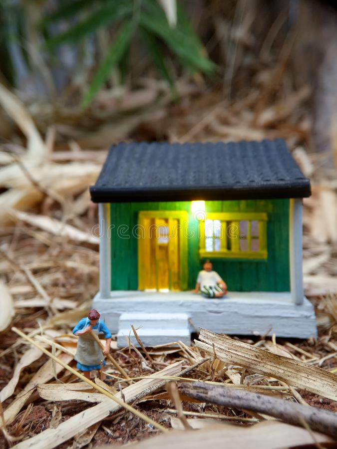 Mini figure toy Indonesian woman cleaning the terrace and old man using sarung, kopiah and white shirt, sit at his house, beyond royalty free stock photography