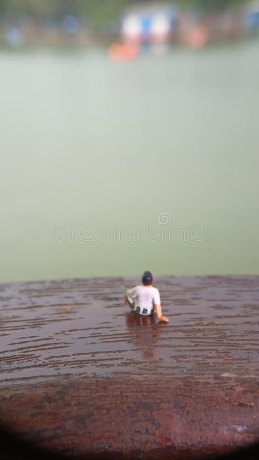 Simple, Mini figure toy old man sit at scratch wooden balcony at river side with copy or negative space for text placement area stock images