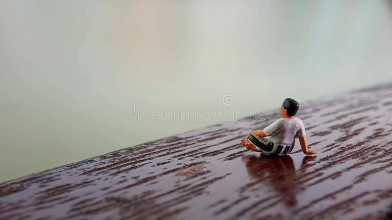 Simple, Mini figure toy old man sit at scratch wooden balcony at river side with copy or negative space for text placement area royalty free stock photo
