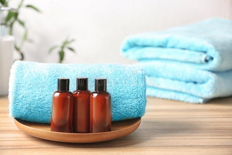Mini- flaskor med kosmetiska produkter och handdukar på tabellen arkivfoto