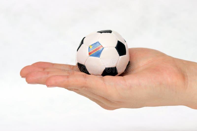 Mini- fotboll i hand och en svart punkt av fotboll är flaggan för DR Congo på vit bakgrund arkivfoton