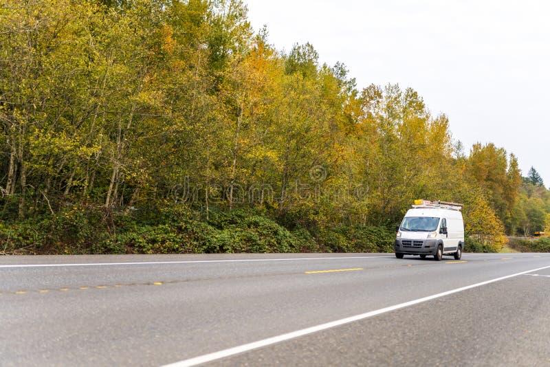 Mini fourgon compact avec des chefs sur le toit conduisant sur la route d'automne avec les arbres jaunes images libres de droits