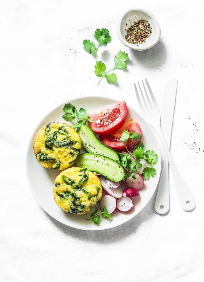 Mini frittata de cheddar d'épinards et salade de légumes sur le fond clair, vue supérieure Configuration d'appartement de table d images libres de droits