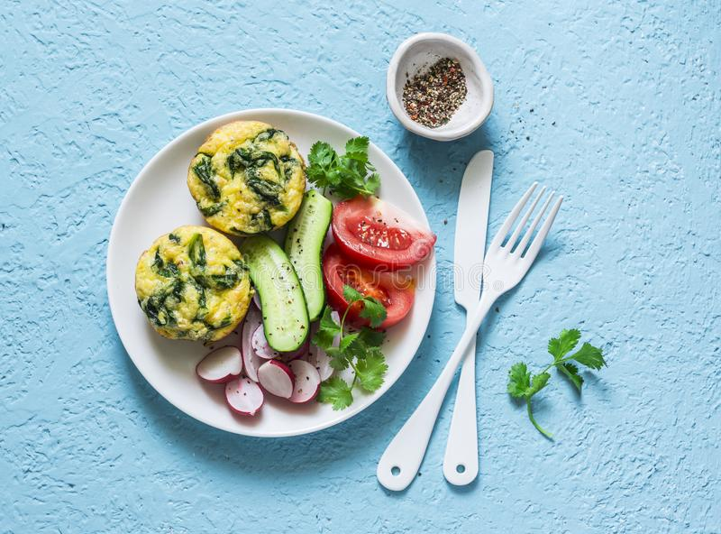Mini frittata del Cheddar de la espinaca y ensalada de las verduras en el fondo azul, visión superior Desayuno, bocado, aperitivo fotografía de archivo libre de regalías