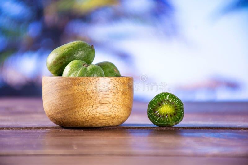 Mini fruta de kiwi verde fresca del bebé con la palma cada uno detrás fotos de archivo libres de regalías