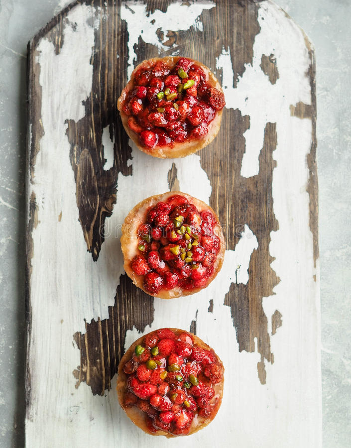 Mini-gâteau au fromage trois fait maison avec les fraisiers communs image stock