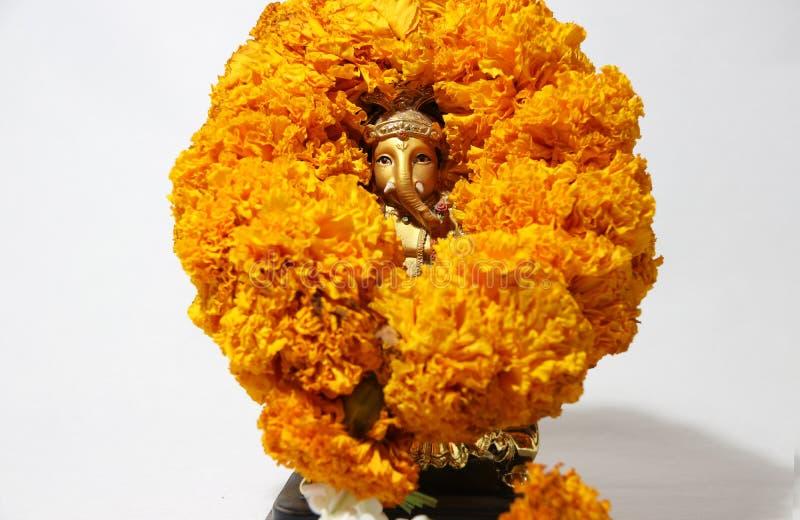 Mini Ganesha hizo de latón con la flor de la maravilla del amarillo de la guirnalda y el fondo blanco fotos de archivo libres de regalías