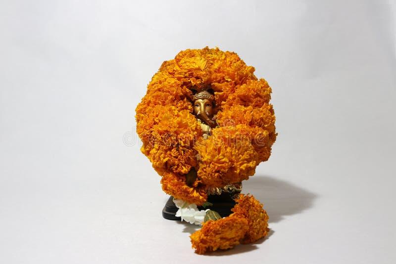 Mini Ganesha hizo de latón con la flor de la maravilla del amarillo de la guirnalda y el fondo blanco foto de archivo libre de regalías