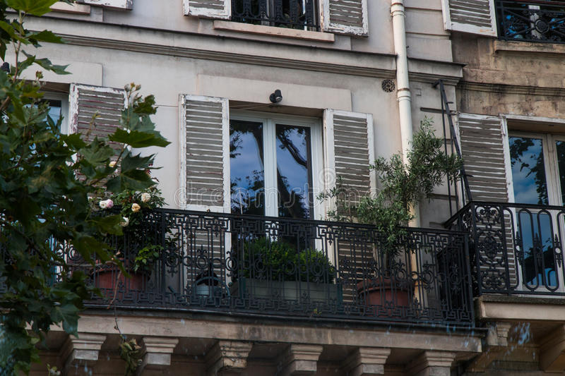 Mini garden on French balcony. Parisian apartment building with it`s typical French balconies, but still room enough to create a mini garden stock photography