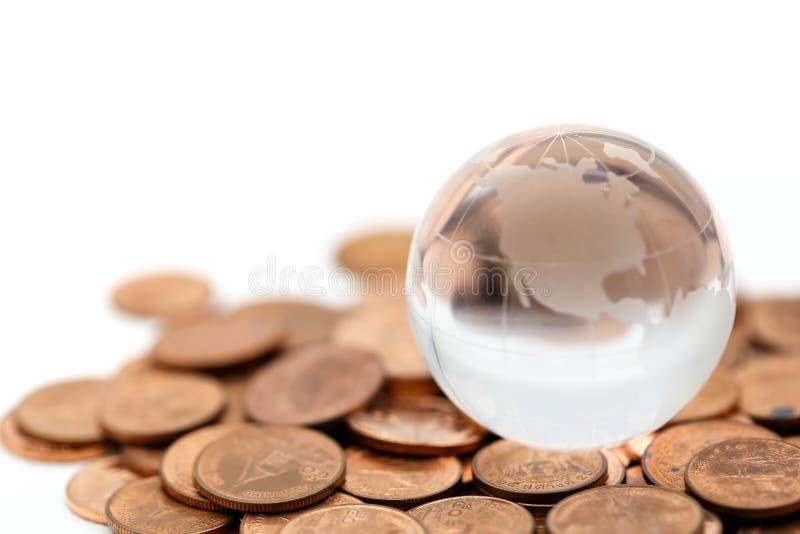 Mini- glass jordklotslut upp med bunten av mynt genom att använda som backgroun royaltyfria foton