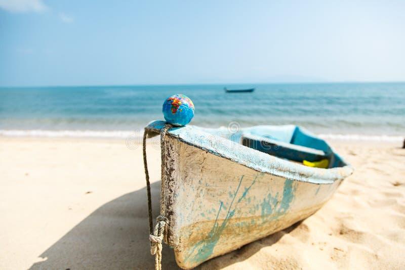 Mini globe sur un bateau sur le fond d'océan photos stock